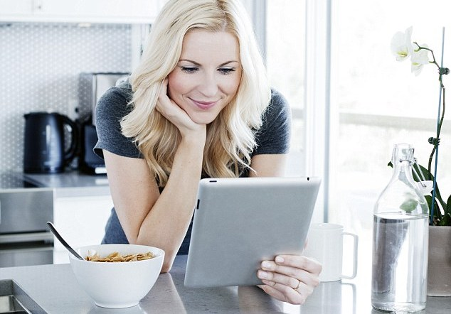 Blonde woman having breakfast and using tablet computer