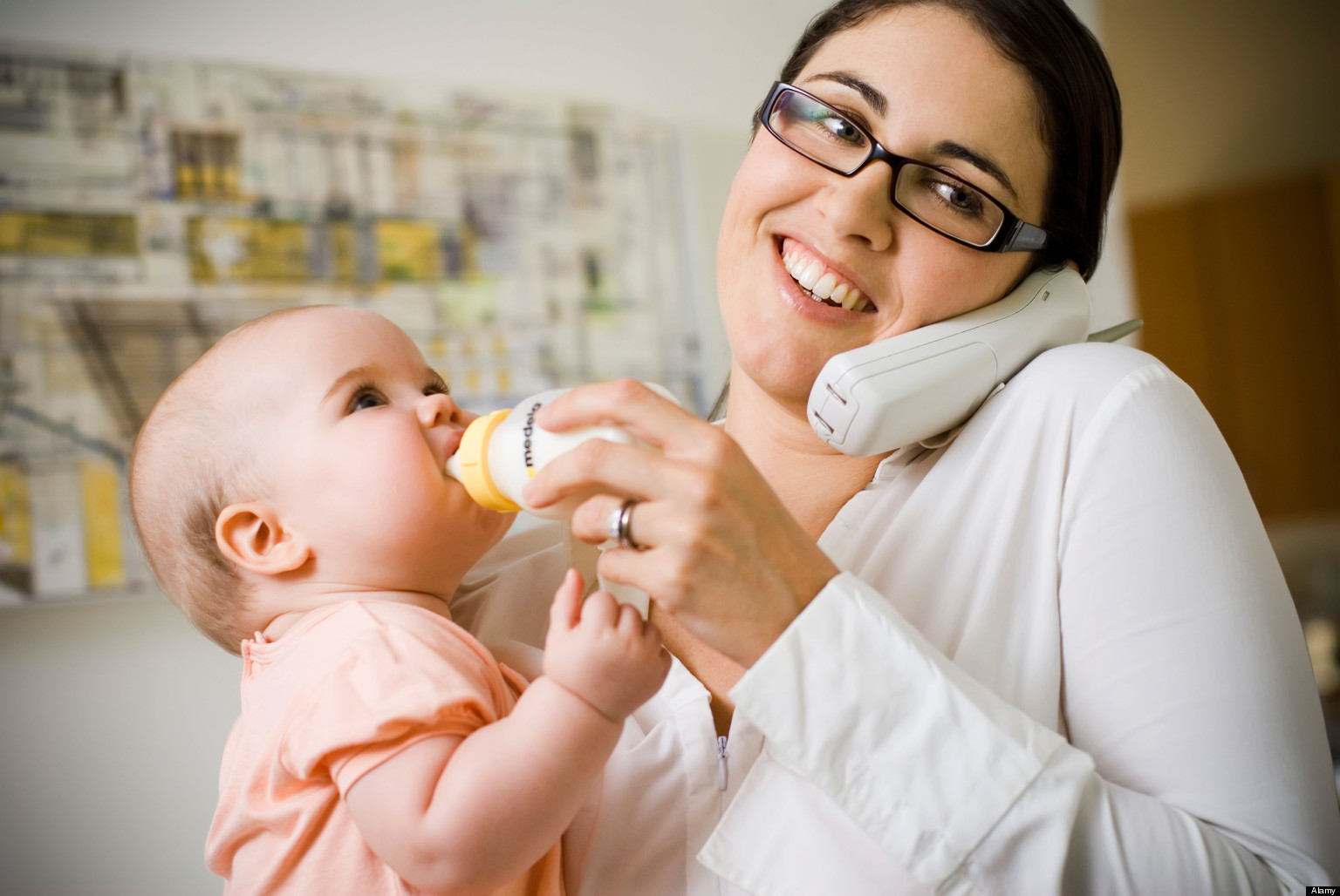 Mother feeding baby while on phone