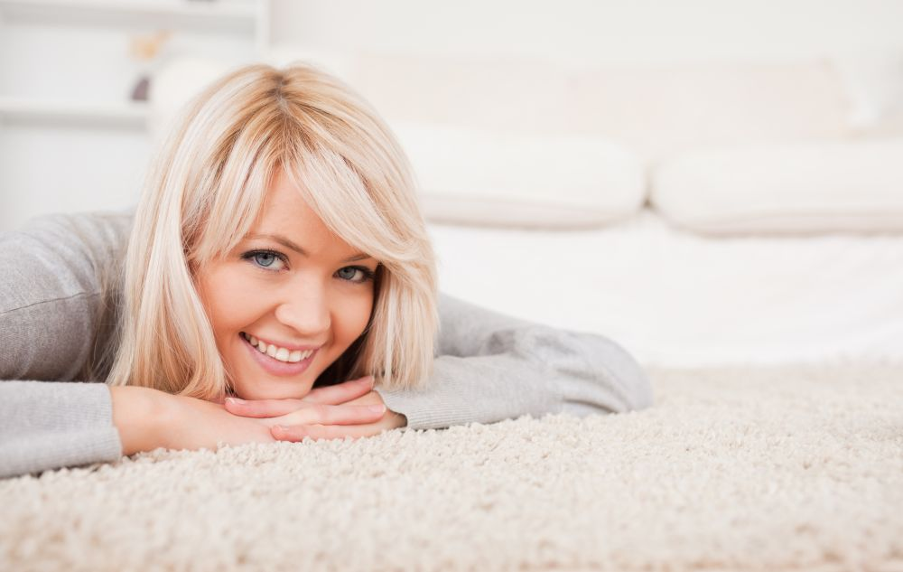 Charming blond woman posing lying down on a carpet in the living