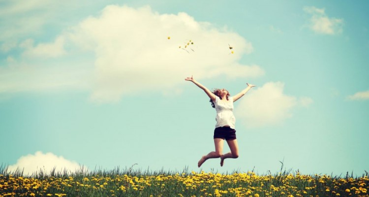 Happy woman jumping on blossom meadow. Beautiful day on field.