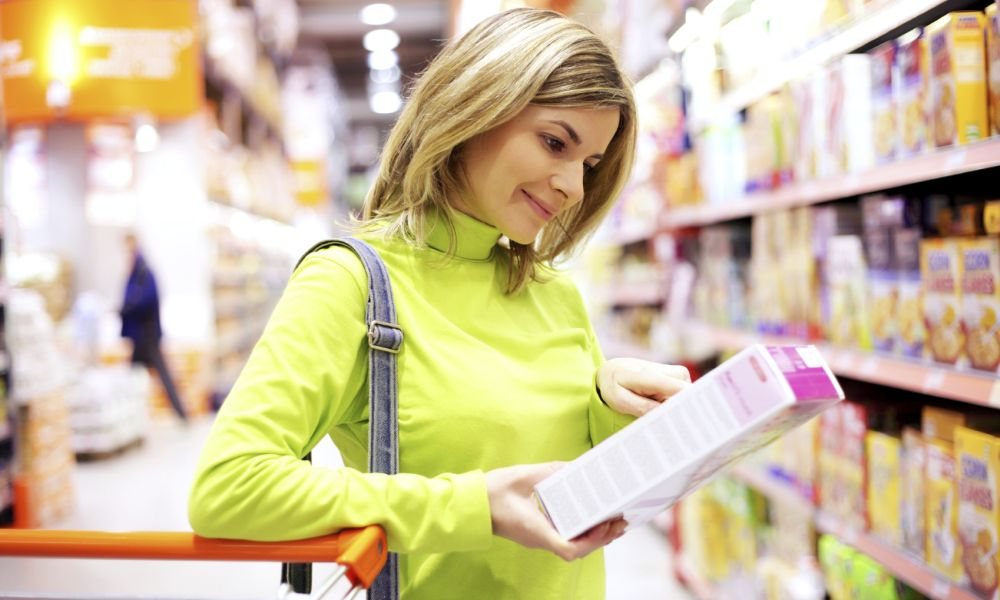 Female checking food labeling in supermarket.