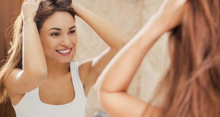 Starting day with smile. Beautiful young woman touching her hair with hands and smiling while standing in front of the mirror