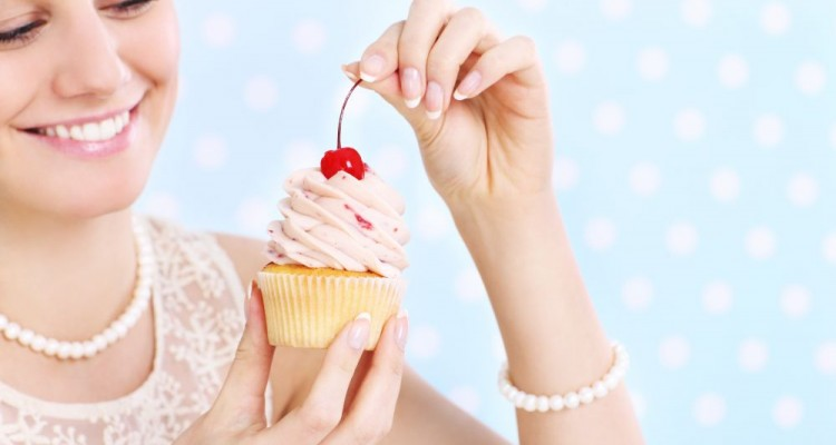 A picture of a young happy woman posing with a cupcake over white and blue background