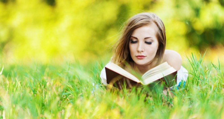 pretty woman lying clearing grass reading book