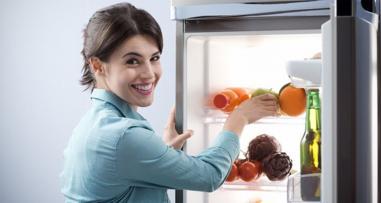 Young cheerful woman taking a green apple from refrigerator and smiling at camera.