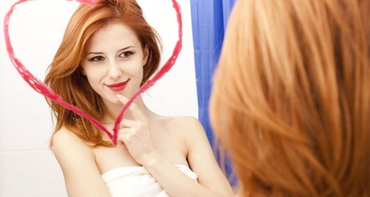 Redhead girl near mirror with heart at it in bathroom.