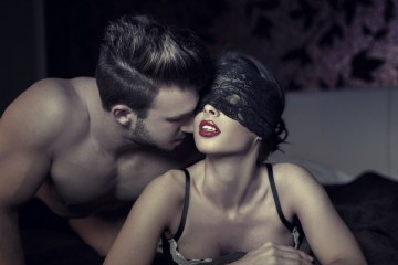 Sexy couple at night in bed, milf with lace eye cover and young lover (Fotolia)