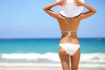 Beach vacation. Hot beautiful woman in sunhat and bikini standin