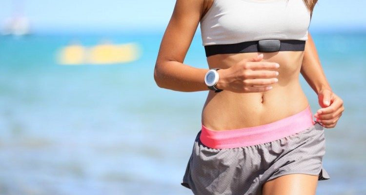 Runner woman with heart rate monitor running on beach with watch