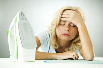 Bored woman with closed eyes and hand on her forehead is leaning on the ironing board.