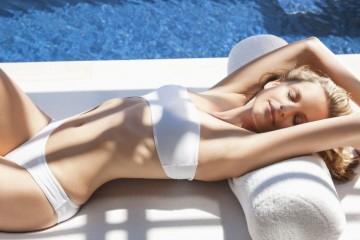 Sexy woman in bikini laying on lounge chair at poolside