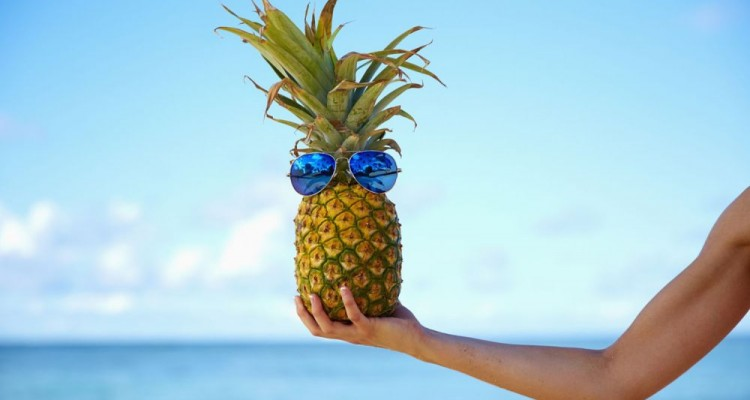 Pacific Islander woman holding pineapple with sunglasses