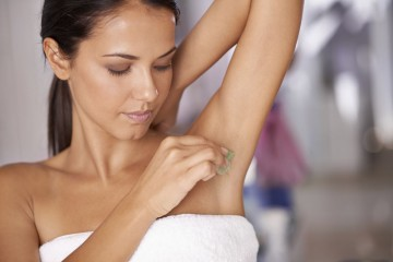 Shot of a young woman waxing her under arm