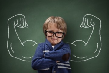 Strong man child showing bicep muscles concept for strength, confidence or defense from bullying