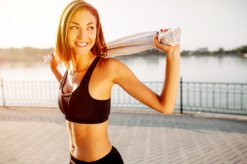 Portrait of an athletic girl. Beautiful young sport fitness model getting ready for jogging in city park.