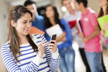Female student texting from her cell phone at the university