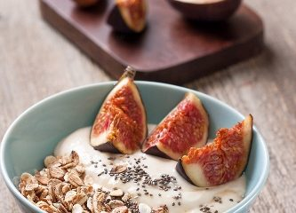Breakfast with muesli yogurt figs and chia seeds in a blue bowl on a wooden background
