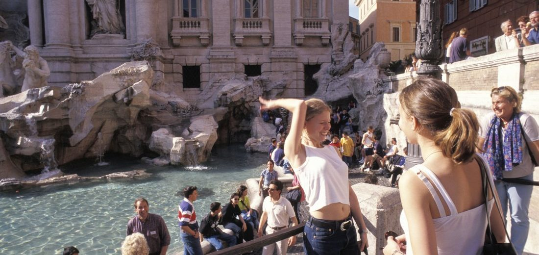 B072J1 Young blond girl student throwing coins into the Trevi Fountain in Rome