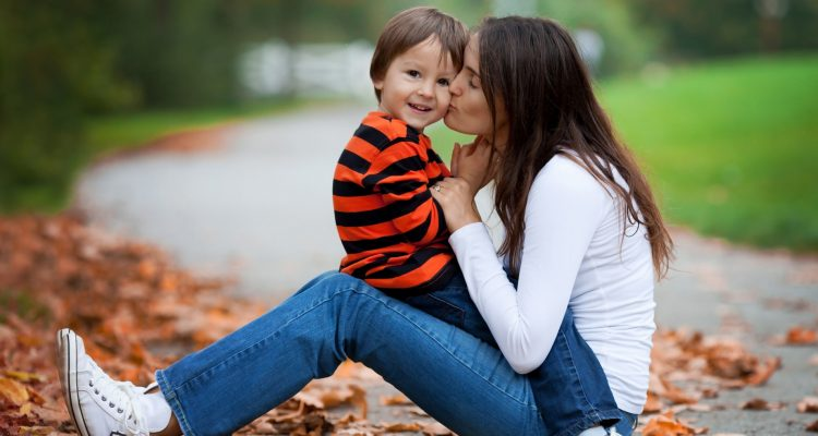 Kid playing isolated portrait. Young mother her boy outdoor in the park