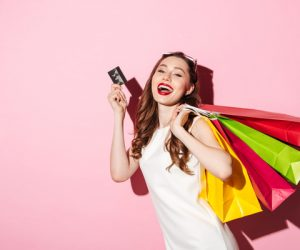 Cheerful young brunette woman holding credit card and shopping bags