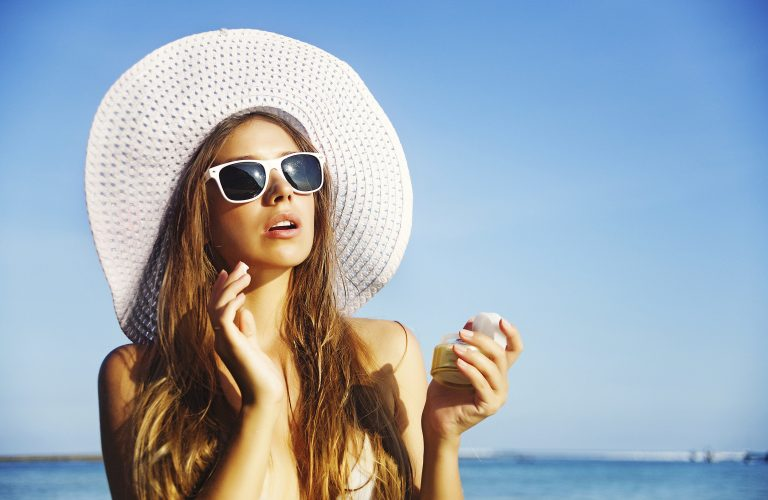 Woman-in-wide-brimmed-hat-and-sunglasses-applying-sunscreen-at-beach-186957862-Credit-iStock