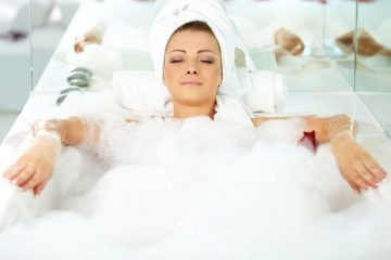 Relaxed young woman lying in a bath tub at home with her eyes closed