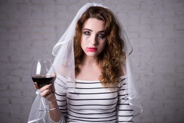 portrait of sad bride crying and drinking red wine