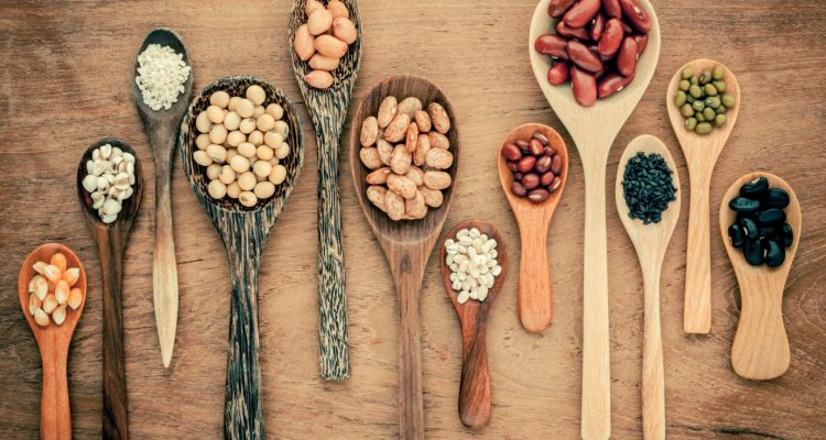 Assortment of beans and lentils in wooden spoon .